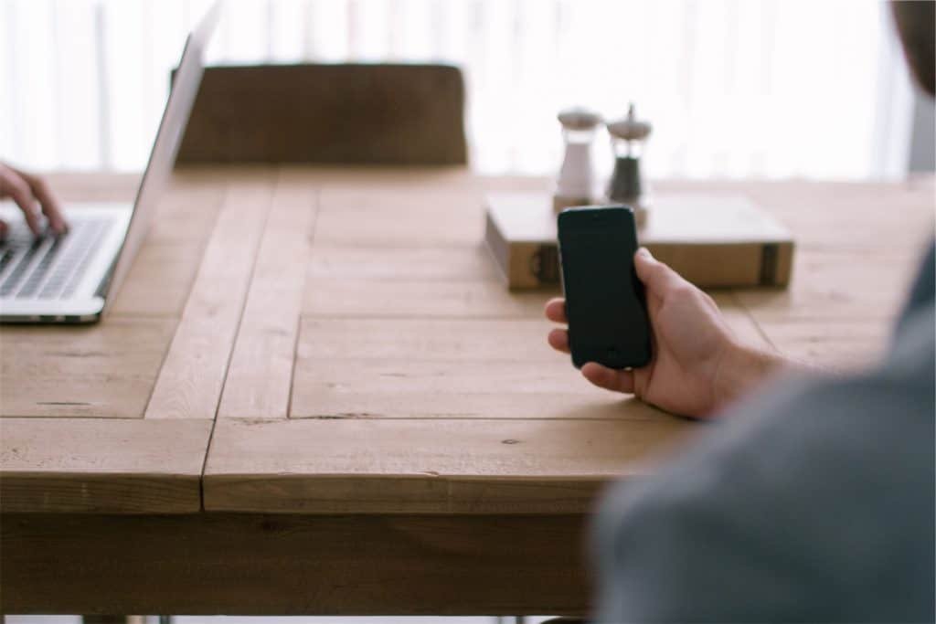 Photo of person holding a phone at a desk for contact page