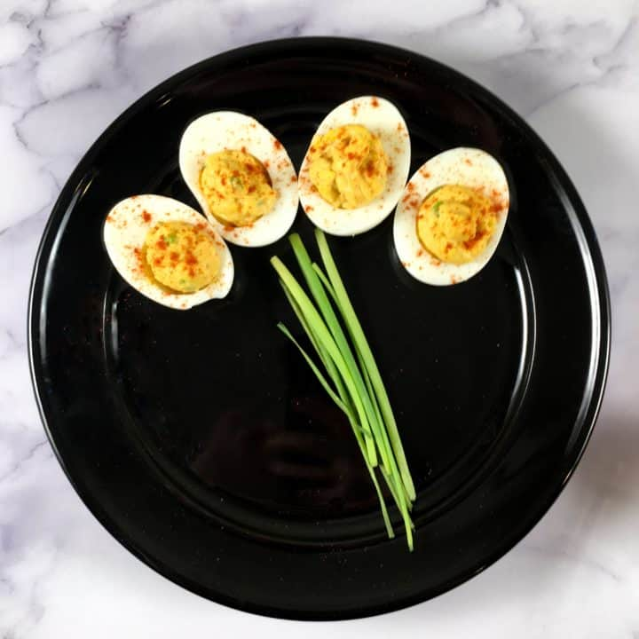 Four easiest deviled eggs with chipotle lime mayo on a black plate with chives