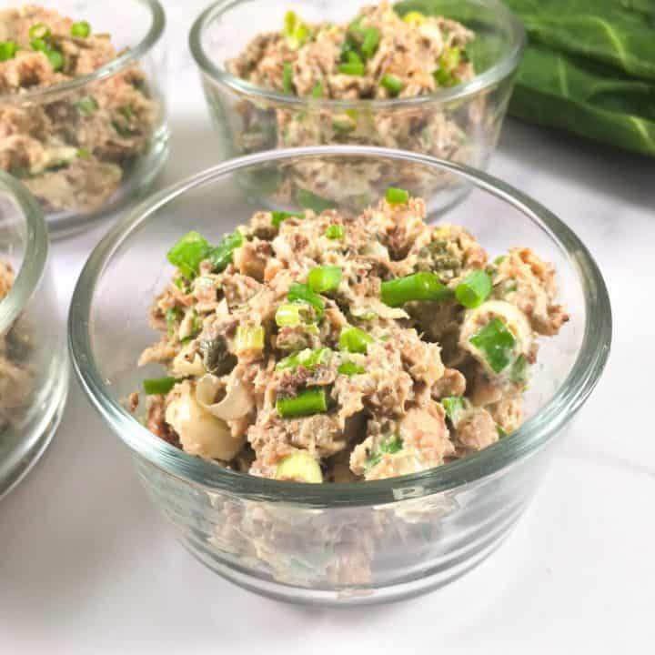 Glass container of sardine salad with collard green leaves in the background