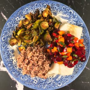 Cherry peach salsa served over white fish with rice and roasted Brussels sprouts on a blue and white plate
