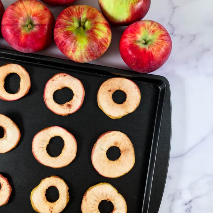 Pumpkin Spice Baked Apple Chips Recipe shown on a black baking tray with apples in the background