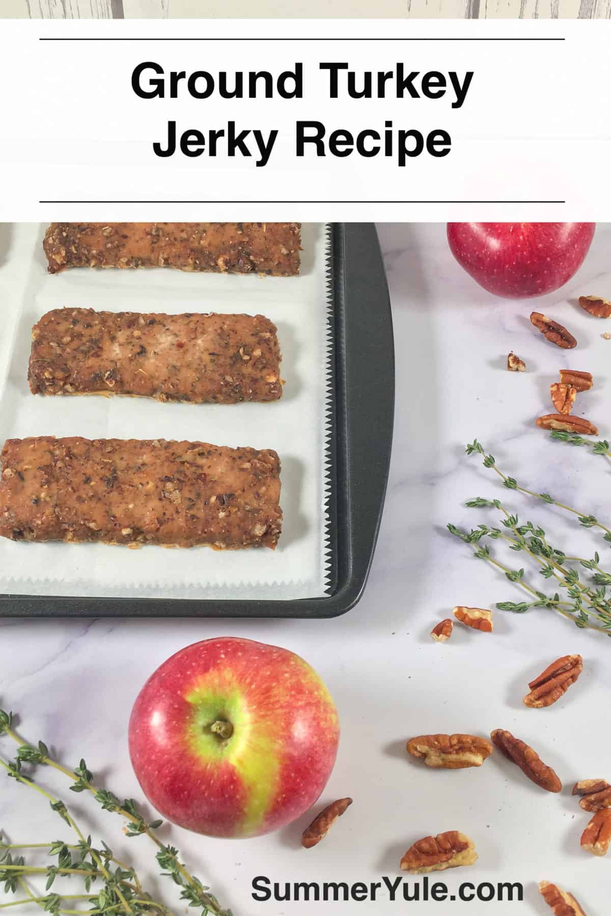 Photo of bars of the ground turkey jerky recipe on a baking sheet, surrounded by thyme, apples, and pecans (long image for Pinterest)