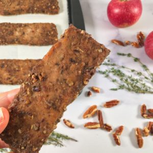 Photo of bars of the ground turkey jerky recipe on a baking sheet, surrounded by thyme, apples, and pecans (square image)