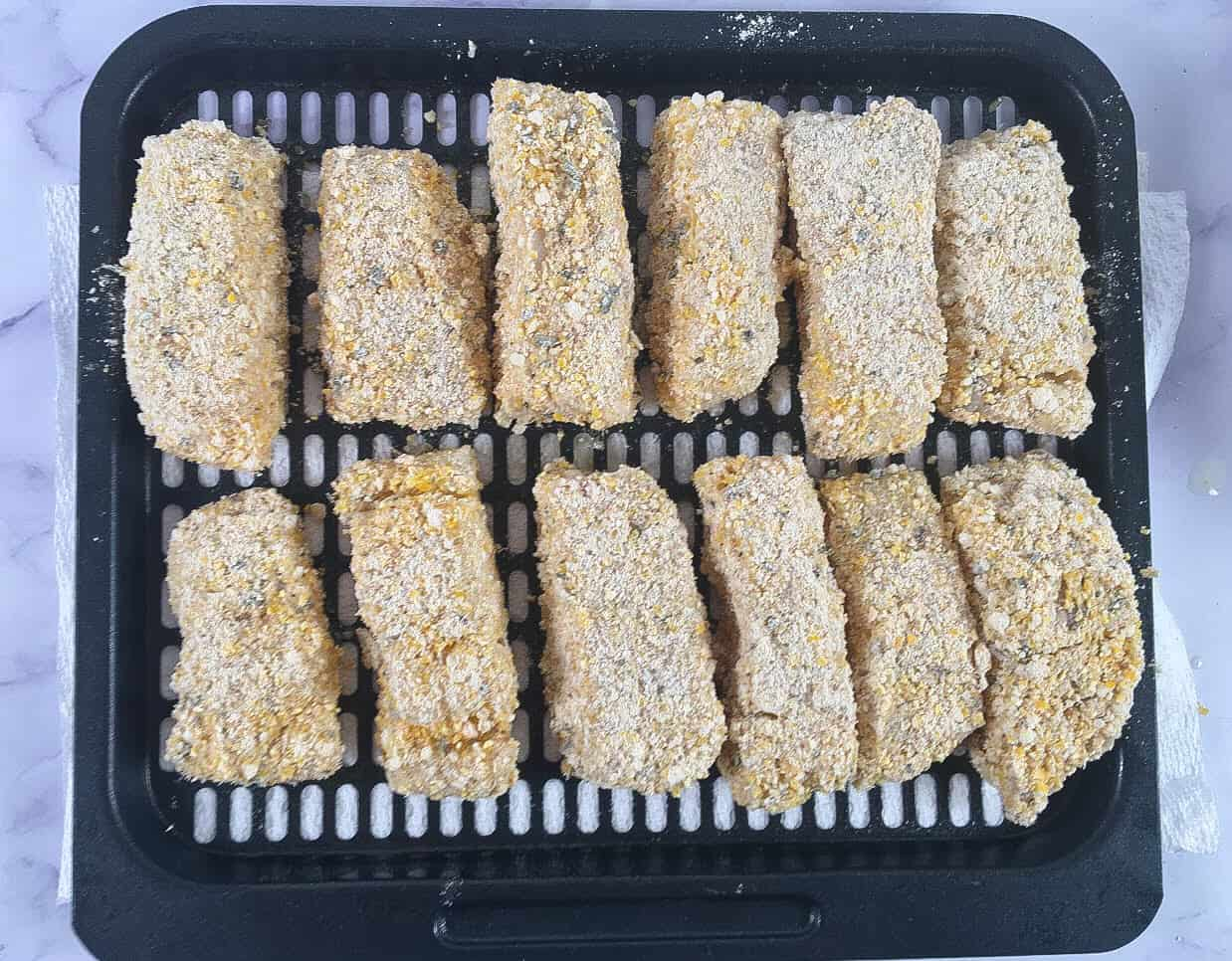Uncooked breaded fish sticks on an air fryer tray