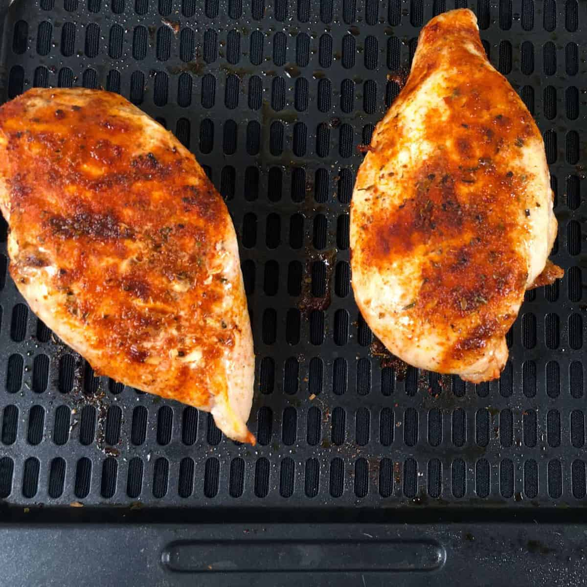 Seasoned chicken breasts on air fryer racks