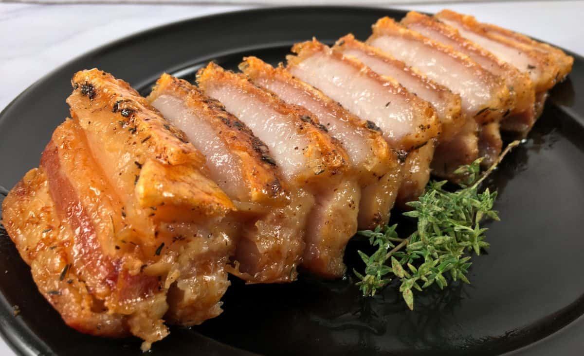 sliced air fried pork belly with thyme on the side