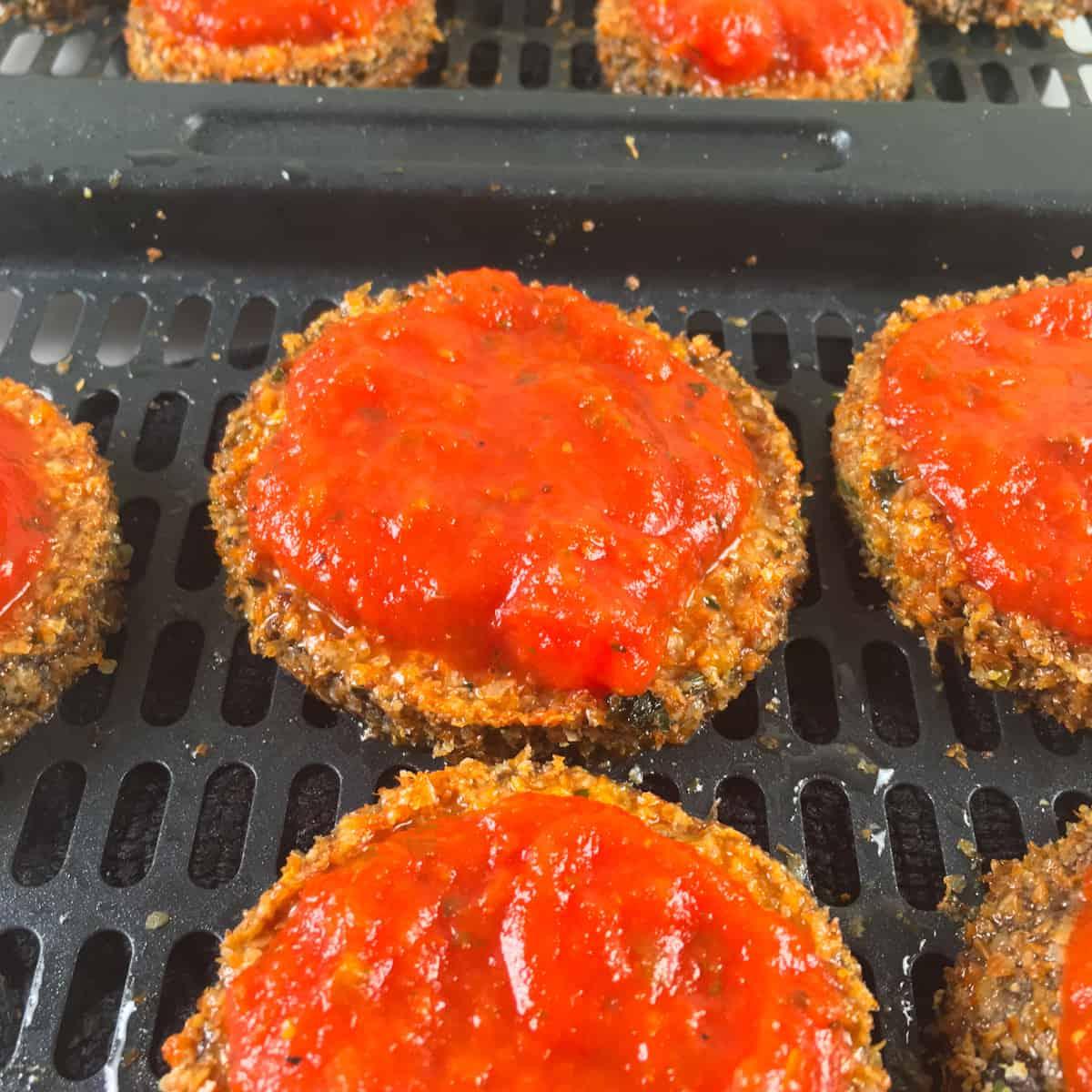 marinara sauce on breaded eggplant slices